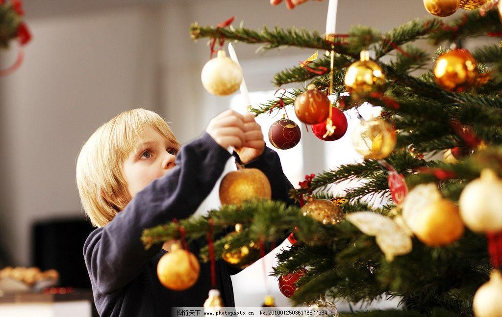 国外欧洲圣诞节小孩子挂礼品在圣诞树图片
